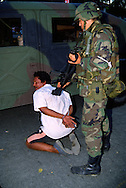 A US soldier takes control of a prisoner as the Americans move to secure a neighborhood from Panamanian army troops during the US invasion of Panama, December 1989.