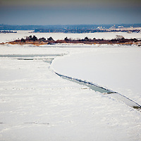 As seen from atop of the Highlands bridge, Highlands New Jersey the Shrewbury River has completely frozen over with ice due to a extended period of freezing temperatures.    The land mass is Sandy Hook National Gateway recreation area park.