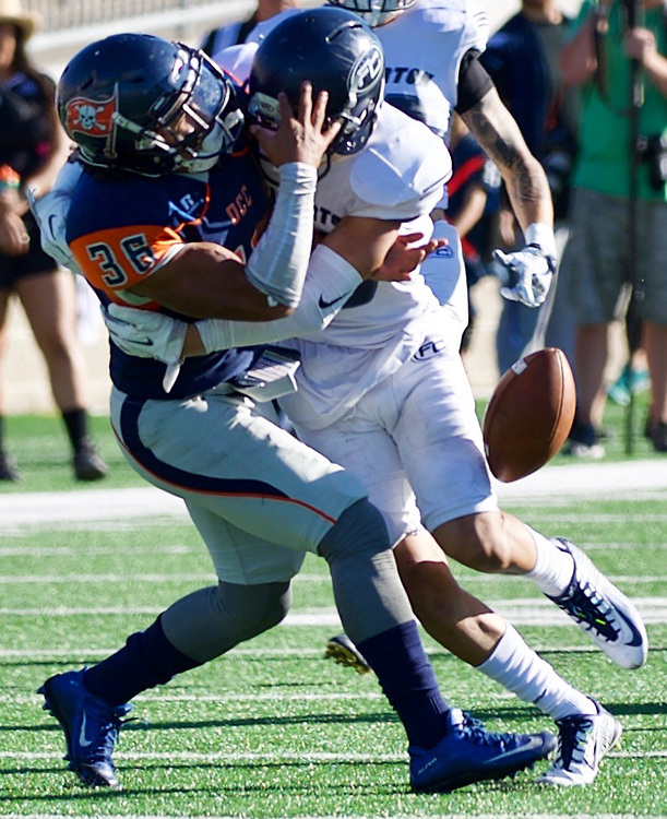 Orange Coast College running back, John Simmons (36) is separated from the ball on a second half punt by Fullerton College.