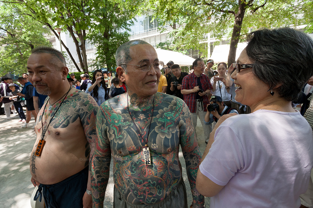 Heavily tattooed men, possibly members of Japan's organised crime groups the Yakuza , show off their tattoos during the Sanja matsuri, Asakusa, Tokyo, Japan. Sunday May 21st 2017. The Sanja matsuri (Three shrines festival) is one of the biggest Shinto festivals in Japan. It takes place for 3 days around the third weekend of May and features over 100 large and small mikoshi, or portable shrines, which are paraded around the streets of the historic Asakusa district in Tokyo. to bring blessings and good luck on the inhabitants. The events attracts up to 2 million visitors each year.