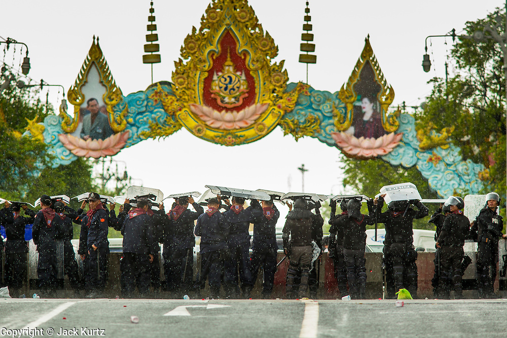 23 NOVEMBER 2012 - BANGKOK, THAILAND:  Thai riot police uses their shields as umbrellas when they were caught in sudden downpour during training for a large anti-government protest in Bangkok Friday. Thai authorities have imposed the Internal Security Act (ISA), that enables police to call on the army if needed to keep order, and placed thousands of riot police in the streets around Government House in anticipation of a large anti-government protest Saturday. The group sponsoring the protest, Pitak Siam, said up to 500,000 people could turn out to protest against the government. They are protesting against corruption in the current government and the government's unwillingness to arrest or pursue fugitive former Prime Minister Thaksin Shinawatra, deposed in 2006 coup and later convicted on corruption charges. The current Thai Prime Minister is Yingluck Shinawatra, Thaksin's sister.      PHOTO BY JACK KURTZ