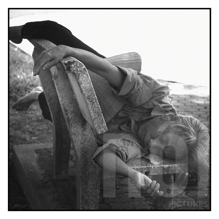 Portrait of an old vietnamese woman sleeping astride a bench in a park close to Ly Thai To street in Hanoi.
