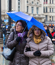 Two women peer out from beneath their umbrella at Piccadilly Circus. As forecasters predicted, the rain arrives in London where Londoners and tourists go about their business. London, February 13 2018.