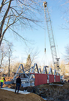 Mark Roberts operates the crane maneuvering the bridge into place with Ron Mitchell and Chris Clairmont guiding the placement on the Belmont Mill side in Belmont Village Monday morning.  (Karen Bobotas/for the Laconia Daily Sun)