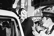 Japan,  Tokyo, 1 November 2016. A Police officer tries to push a fox masked participant back into his vehicle. In Japan, foxes are seen as magical creature bound to play tricks.