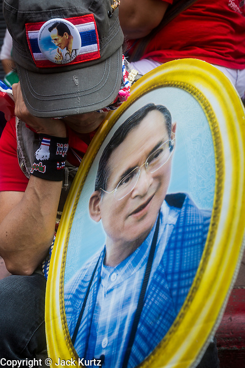 01 FEBRUARY 2014 - BANGKOK, THAILAND:  An anti-government protestor naps while holding a portrait of Bhumibol Adulyadej, the King of Thailand. The protestors charge the government of Yingluck Shinawatra doesn't adequately support the monarchy and frequently carry pictures of the King during the protests. The anti-government protest movement, led by the People's Democratic Reform Committee (PDRC) organized a march through the Chinatown district of Bangkok Saturday and disrupted the city's famous Chinese New Year festival. Some streets were blocked and protest leader Suthep Thaugsuban walked through the neighborhood collecting money. The march was in advance of massive protests the PDRC has promised for Sunday, Feb. 2 in an effort to block Thais from voting in the national election.    PHOTO BY JACK KURTZ
