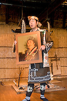 An Ainu man shows a picture of an Ainu woman with traditional mouth tattoos.