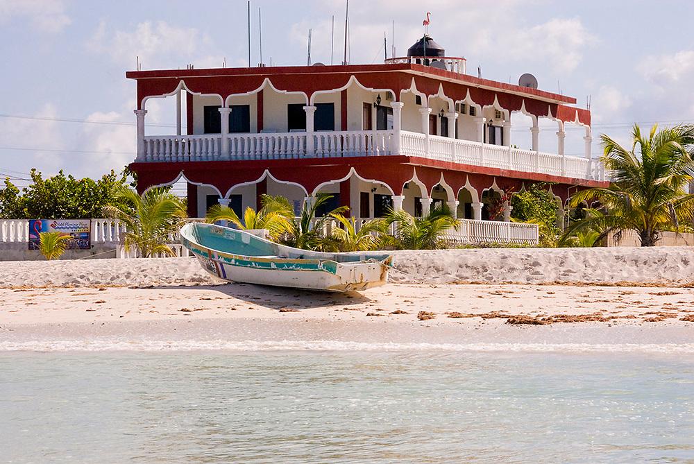 Celestun, Mexico -Jan 18 :  Beachfront hotel and empty boat moored on the tropical white sandy beach on 18 Jan 2007 at Celestun