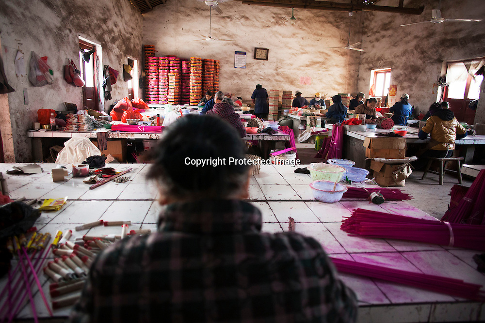 Hunan, Liuyang, Dec. 19..2013 :  rural women assemble firecrackers in a factory that produces firecrakcers for the Western market.