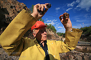 Steve Lukinuk, president of Amethyst Mine Panorama, holds amethyst up to sun to spot embedded gemstones; Dorion, Ontario; Canada.