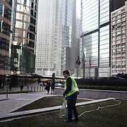 """A woman waters the grass in Central.<br /> <br /> Hong Kong (香港; """"Fragrant Harbour""""), officially known as Hong Kong Special Administrative Region of the People's Republic of China since the hand-over from the United Kingdom in 1997 under the principle of """"one country, two systsems"""".  7 million people live on 1,104km square, making it the most vertivcal city in the world. Hong Kong is one of the world's leading financial centres along side London and New York, it has one of the highest income per capita in the world as well the moste severe income inequality amongst advanced economies. The Hong Kong civil society is highly regulated but has at the same time one of the most lassiez-faire economies with low taxation and free trade. Civil unrest and political dissent is unusual but in 2014 the Umbrella Movenment took to the streets of Hong Kong demanding democracy and universal suffrage. 93 % are ethnic Chinese, mostly Cantonese speaking."""