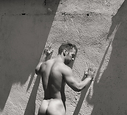nude muscular man against a wall