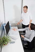 Businessmen pointing at computer screen in office