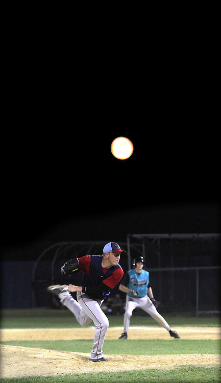 Clarinda A's pitcher Mark Trentacosta  delivers a pitch as a rising moon appears over home field Municipal Stadium.  photo by David Peterson