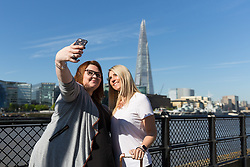 © Licensed to London News Pictures. 05/05/2018. London, UK. Two tourists from Yorkshire take a selfie in front of the London shard during hot and sunny weather near the River Thames in London this morning. Photo credit: Vickie Flores/LNP