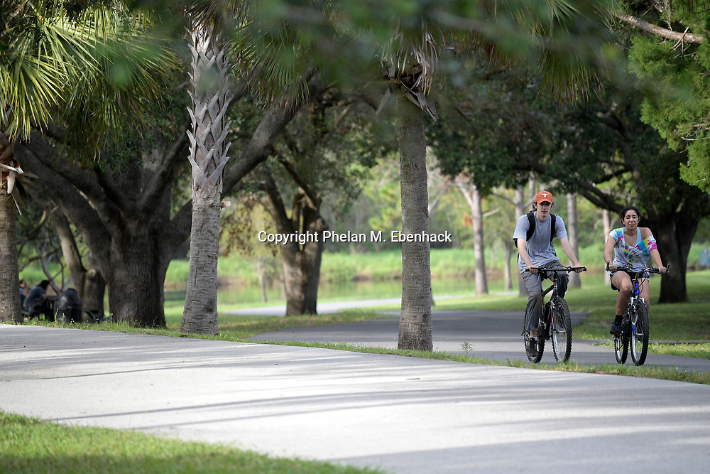 Bicyclists ride along a trail in Jay Blanchard Park Saturday, Oct. 21, 2017, in Orlando, Fla. (Photo by Phelan M. Ebenhack)