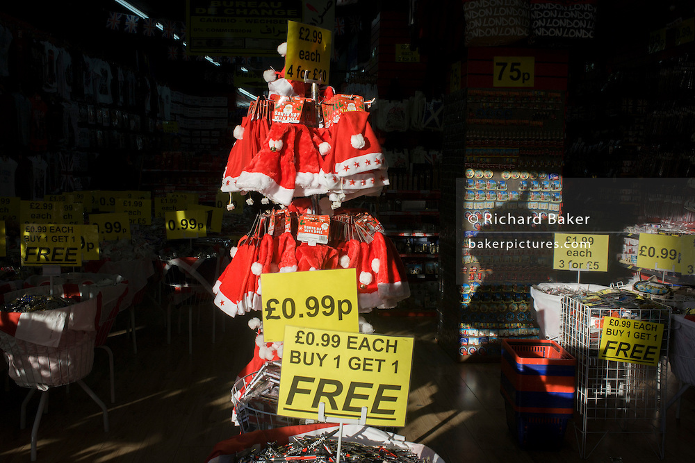 Christmas santa hats on a sunlit rack in a trinket shop on London's Oxford Street.