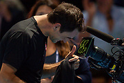 Roger Federer of Switzerland autographs the TV camera lens after winning his match during the Nitto ATP Finals at the O2 Arena, London, United Kingdom on 14 November 2019.