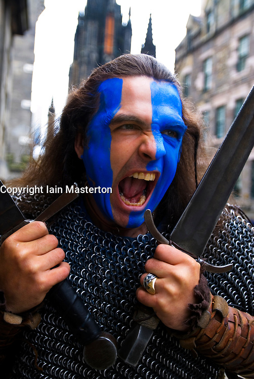Street performer acting Scottish warrior with painted face in Edinburgh Scotland