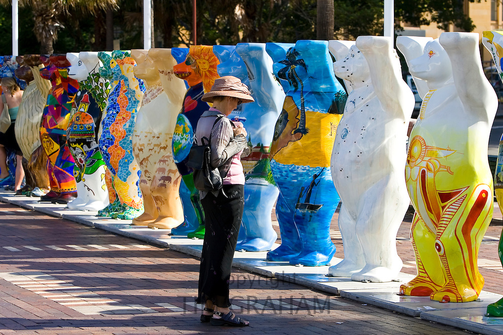 Tourist admires the Unicef charity fundraising United Buddy Bears in Sydney, New South Wales, Australia