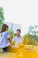 Young attractive business couple talking while sitting on the grass in park