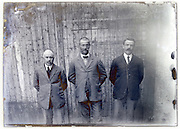 eroding glass plate with three men