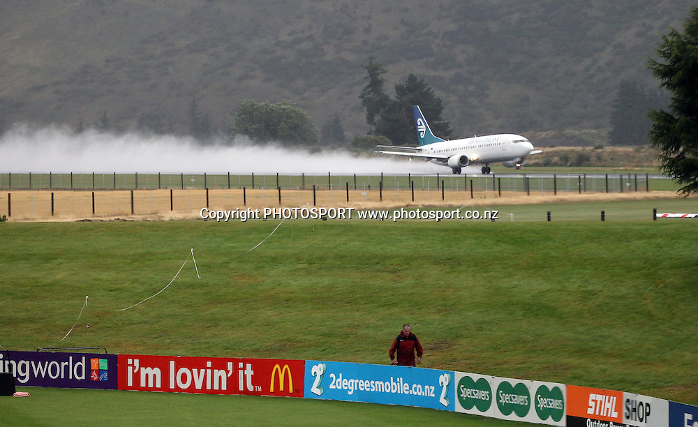 An Air New Zealand jet takes off in the background of a washed out Queenstown Events Centre. 2nd ODI, Black Caps v Pakistan, One Day International Cricket. Queenstown, New Zealand. Wednesday 26  January 2011. Photo: Andrew Cornaga/photosport.co.nz