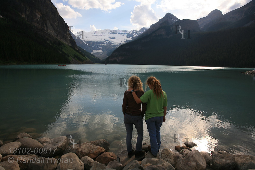Mother and daughter stand along rocky lakeshore enjoying the tranquility of Lake Louise amid the soaring mountains of Banff National Park in the Canadian Rockies; Alberta, Canada.