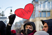 """MADISON, WI — FEBRUARY 13, 2015: Student Nick Shay holds a heart-shaped protest sign during the """"Stop the Cuts"""" Rally on Library Mall, Saturday, February 14, 2015. The rally drew hundreds of student, faculty and community supporters in spite of the cold Midwest weather."""