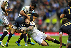Horacio Agulla (Argentina) is double-tackled by Billy Vunipola and Joe Marler (both England) - Photo mandatory by-line: Patrick Khachfe/JMP - Tel: Mobile: 07966 386802 09/11/2013 - SPORT - RUGBY UNION -  Twickenham Stadium, London - England v Argentina - QBE Autumn Internationals.