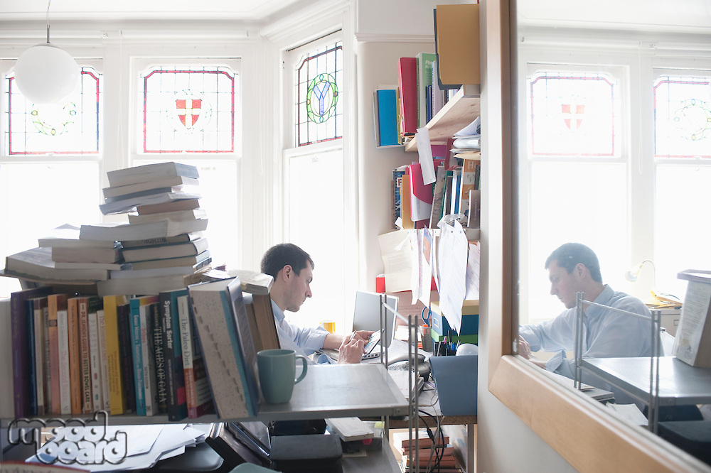 mid adult man working in cluttered study