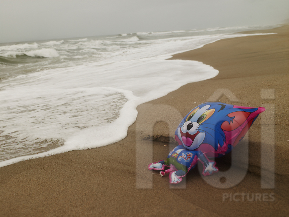 A balloon of Tom the Cat lays abandoned in the sand along the shore of Hoi An, Vietnam, Southeast Asia