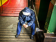 13 AUGUST 2013 - HONG KONG: A Star Ferry worker takes shelter on a ferry gangway and waits out rains from Typhoon Utor in Hong Kong. Typhoon Utor (known in the Philippines as Typhoon Labuyo) is an active tropical cyclone located over the South China Sea. The eleventh named storm and second typhoon of the 2013 typhoon season, Utor formed from a tropical depression on August 8. The depression was upgraded to Tropical Storm Utor the following day, and to typhoon intensity just a few hours afterwards. The Philippines, which bore the brunt of the storm, reported 1 dead in a mudslide and 23 fishermen missing at sea. The storm brushed by Hong Kong bringing several millimeters of rain and moderate winds to the island but causing no reported damage or injuries. It is expected to make landfall in China.   PHOTO BY JACK KURTZ