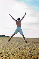 Man on beach doing star jump back view