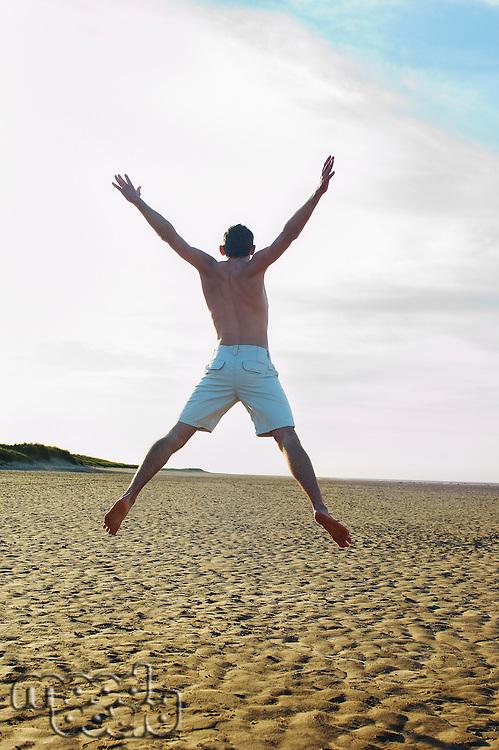 Man on beach doing star jump back view