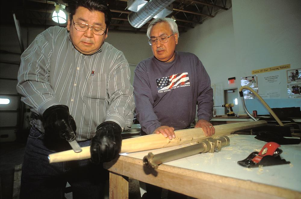 Barrow, Alaska, Native men making a wooden whale harpoon