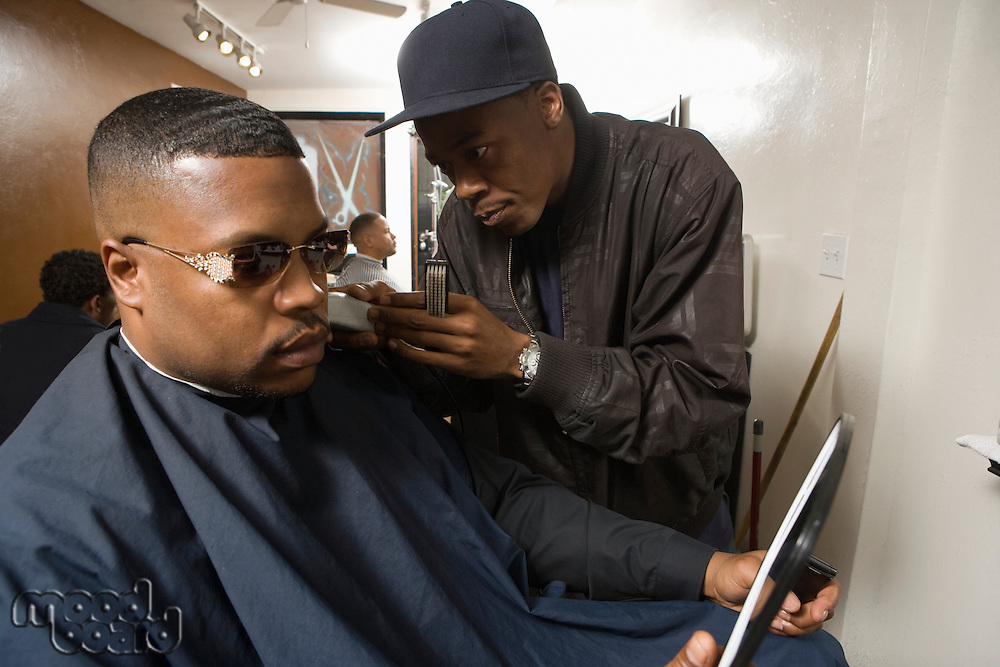 Young man shaving a customers facial hair while he looks in the mirror