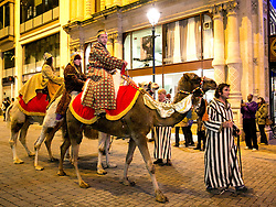© Licensed to London News Pictures. 09/11/2013. Birmingham, UK. Pictured, The Three Kings on camels are led through the streets of Birmingham. Crowds packed Birmingham City Centre to watch the Lord Mayor Switch on the Cristmas Lights and start the Christmas parade. Along with reindeer, panto characters, street artists, musicians, three camels also joined the parade carrying the Three Kings. At the close of the parade it snowed in Victoria Square. Photo credit : Dave Warren/LNP