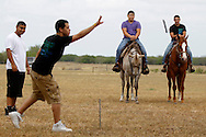 "Seniors Jesus De La Paz (center) and Ernesto Gonzalez watch from atop their horses, ""Goat Cheese"" and ""Goliath,"" as classmate Luis ""Yayo"" Torres tosses a horse shoe May 30, 2012 on the last day of school at Premont High School. De La Paz and Gonzalez rode their horses to school on the last day, and offered rides to other seniors as they celebrated the end of their high school career."