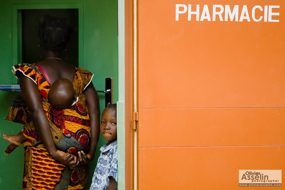 Brou Adjua Thérèse (right) and her children Kwajo Neri, 6, and Kwajo Neri dir Roger, 2, wait to purchase drugs at the pharmacy of the NDA health center in Dimbokro, Cote d'Ivoire on Friday June 19, 2009..