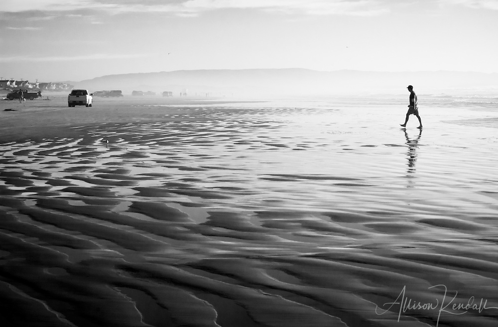 Hazy afternoon light reflects from the wave-swept sands of Pismo Beach in California