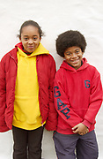Portrait of young black boy smiling with afro and a red Gap hoodie standing next to young black girl in a yellow hoodie, London, 2000's