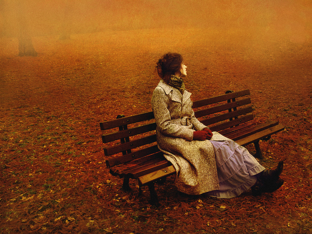 A woman in a coat and red gloves, sitting on a bench in the park covered with autumn leaves.