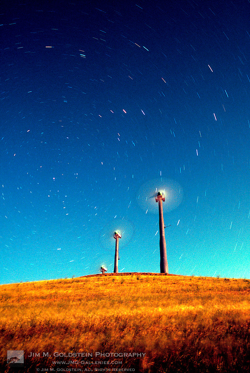 Startrails appearing to be blown by wind turbines under a full moon.