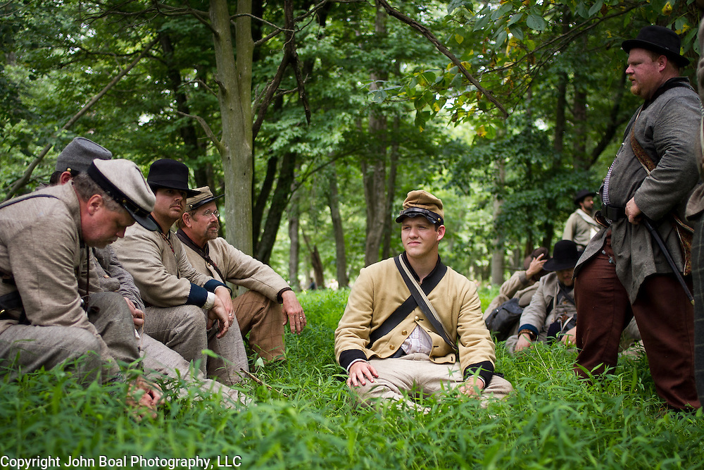 Collin Robinson, 17, center, of Oxford, Alabama, rests in the shade with other reenactors prior to participating as the 47th North Carolina in Pickett's Charge, during the Sesquicentennial Anniversary of the Battle of Gettysburg, Pennsylvania on Sunday, June 30, 2013.  A pivotal moment in the Civil War, over 50,000 soldiers were killed, wounded or missing after 3 days of battle from July 1-3, 1863.  Later that year, President Abraham Lincoln returned to Gettysburg to deliver his now famous Gettysburg Address to dedicate the cemetery there for the Union soldiers who died in battle.  John Boal photography
