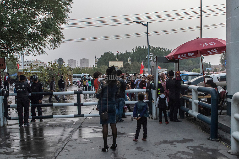 Kashgar. October 1st, 2017<br /> Uyghur waiting in line at a police checkpoint where they will have their Id checked,