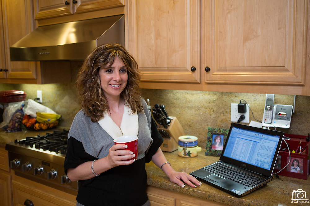 Joy Hahn, Business Development Manager, of Cornerstone Technologies talks with her family over a cup of coffee as her husband helps their 11-year-old daughter with homework in the kitchen of their home in San Jose, California, on March 25, 2013.  (Stan Olszewski/SOSKIphoto)