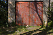 Padlocked peeling garage doors of an old stone garage, in a north Somerset farm.