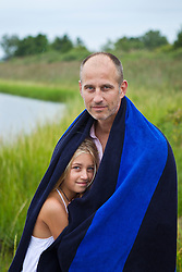 father and daughter under a large towel by the beach