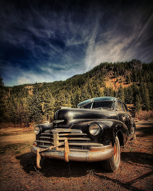 Rusting old car in field with mountains in USA